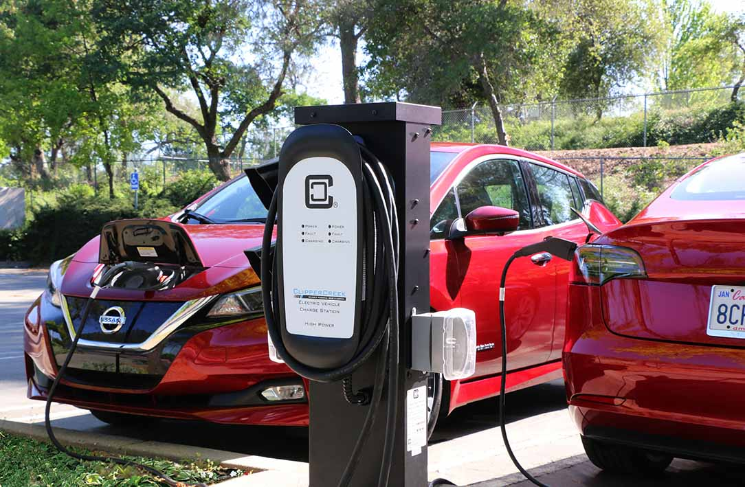 Dual Charging Station Charging Red Tesla and Nissan Leaf